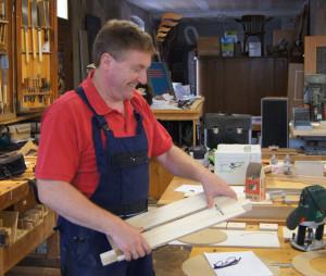 Ein Kursteilnehmer hält eine selbst gebaute Schablone in der Hand und freut sich offensichtlich darauf, damit zu fräsem.