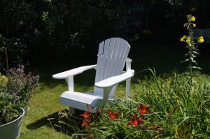 weißer Adirondack chair im Garten