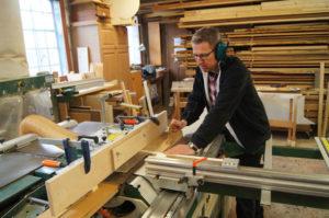 Ein Kursteilnehmer fräst an der Tischfräse eine Schlitz und Zapfen-Verbindung an der Tischfräse. Zu sehen ist das Vorsatzbrett mit Schutzplatte, welches ein sicheres Arbeiten ermöglicht