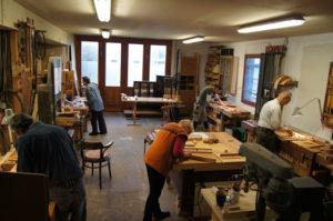 Funf Teilnehmer arbeiten an Hobelbänken und sägen und stemmen