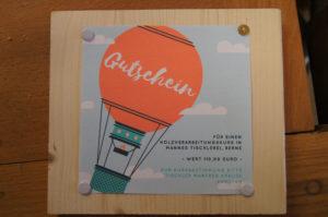 mit Heftzwecken auf einem Brett befestigtes Blatt zeigt einen Heißluftballon. Text: Gutschein über einen Kurs in Mannes Tischlerei.