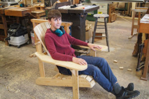 junger Kursteilnehmer sitzt auf seinem selbst hergestellten Adirondack chair probe