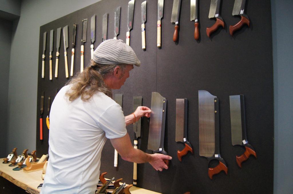 Manne steht vor einer Werkzeugwand mit Handsägen im Laden von Dieter Schmid